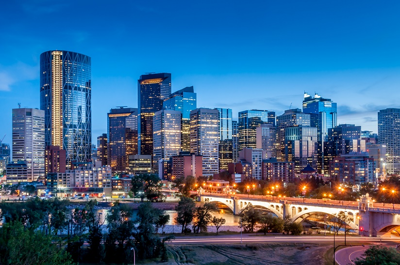 Working holiday Canada. Calgary skyline at night with Bow River and Centre Street Bridge.