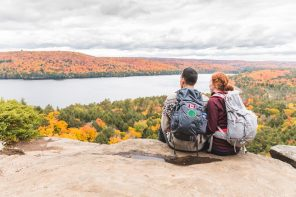 Working holidays canada. Couple looking at panorama from the top of the rocks. Two young hikers staring at the beautiful view below them with colourful trees all around. Wanderlust feeling, hiking and nature concepts.