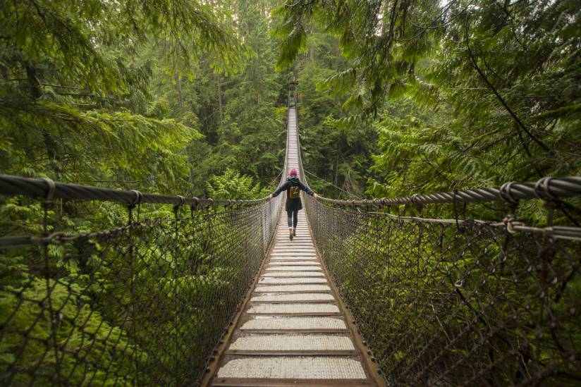 Woman on Lynn canyon suspension bridge, North Vancouver, British Columbia, Canada