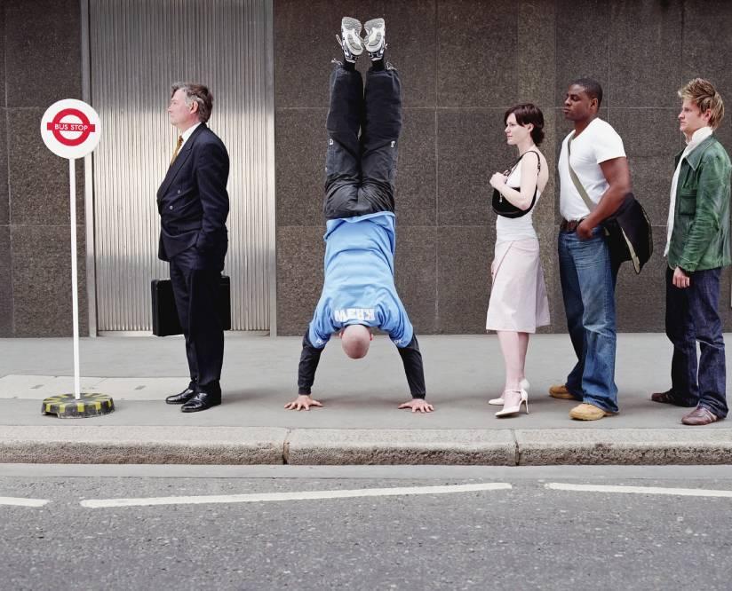 Man doing Handstand in Queue