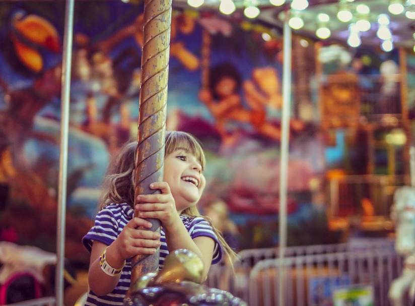 Happy little girl on a merry go round filled with joy