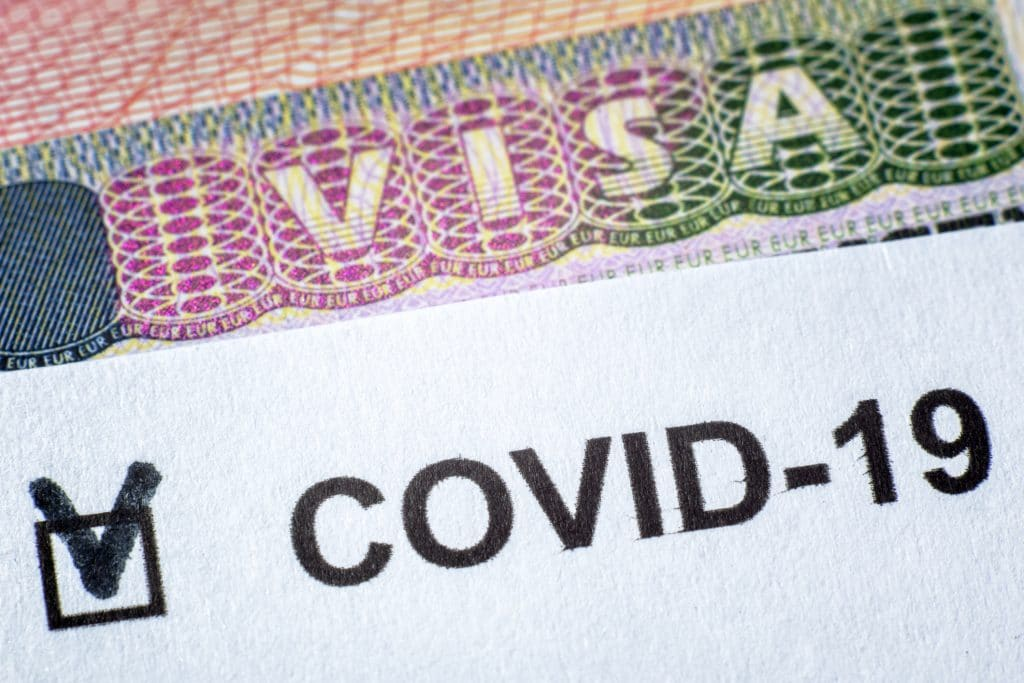 COVID-19 coronavirus pandemic and travel concept, document with COVID positive test and Visa stamp in passport.